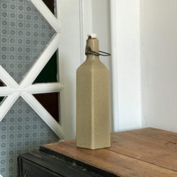 Bouteille en grès vernissé beige de forme hexagonale avec bouchon capsule en céramique estampillée d'une cigogne, grès d'Alsace