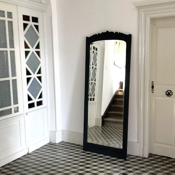 Grand miroir en bois sculpté fleurs peint en noir libéron