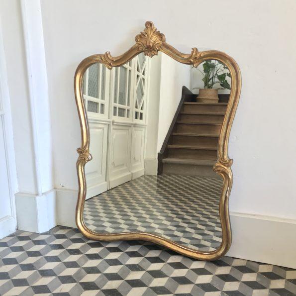 miroir ancien de forme chantournée en bois mouluré, sculpté et doré avec fronton à décor de coquille et de feuilles d'acanthe
